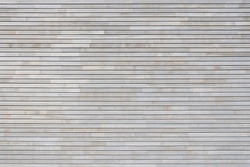 New light gray wood paneling made of narrow horizontal boards on a facade