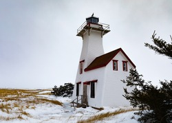 New London Lighthouse historic light station building in Kensington County of Prince Edward Island, PEI, Canada, in winter with snowy sand dunes