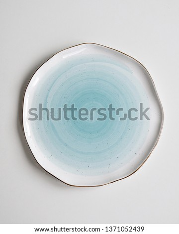 New luxury cutlery view from above on a isolated white background. Top view. Porcelain blue saucer with gold ring. Trendy plate pastel shades. Flat lay view.