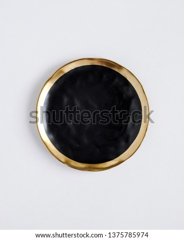 New luxury elegance cutlery view from above on a isolated white background. Top view. Porcelain black saucer with gold ring. Trendy black plate. Flat lay view.