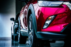 New luxury SUV compact car parked in modern showroom for sale. Car dealership office. Car retail shop. Electric car technology and business concept. Automobile rental concept.