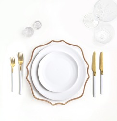 New luxury white ceramic plate, golden cutlery view from above on a isolated background. Top view. Knife and fork for a festive table for a wedding, birthday or party.