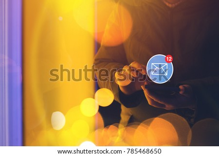 New message notification icon on smartphone, woman using mobile phone on the street at night #785468650