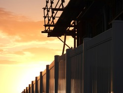 New Metal Shiny Fence and Scafold Construction Site silhouette against a Colorful Sunset Sky