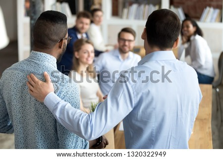 New mixed race employee having first working day in company standing in front of colleagues, executive manager employer introducing welcoming newcomer to workmates. Human resources employment concept