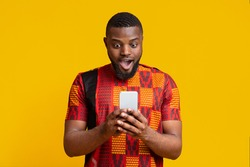 New mobile app. Amazed black guy in authentic t-shirt looking at smartphone screen over yellow background