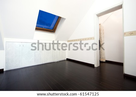 New modern attic room with a roof skylight window and wall cabinet
