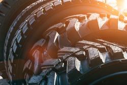 New modern black truck tire wheels in sunlight, close up