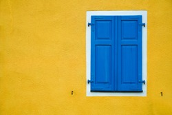 new modern blue closed Shutters, yellow wall of residence house.