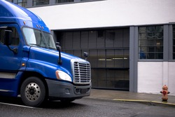New modern blue large class 8 semi truck with trailer for long haul and local transportation and delivery of cargo and goods from warehouses to retail outlets and businesses on city street
