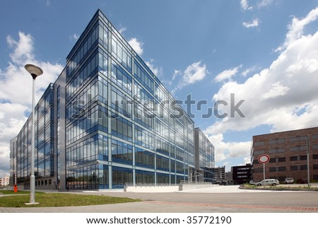 New modern futuristic building and blue skies in cloudy day - stock photo