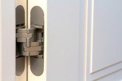 New modern metal door hinges on white wooden doors.