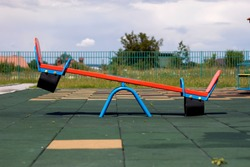 New modern plastic bright colorful blue and red empty toy seesaw swing on nursery playground with soft rubber flooring on bright sunny summer day. Perfect place for children activities outdoors.