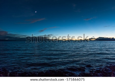 new moon hanging above calm lake