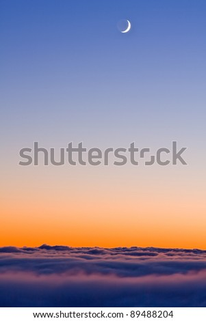 new moon in sky over clouds after sunset