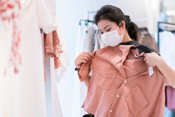 new normal after covid epidemic yound asian female wear face mask protection shopping dress or cloth in boutique shop new lifestyle in department store mall background
