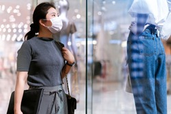 new normal after covid epidemic young asian female wear face mask protection shopping dress or cloth in boutique shop new lifestyle in department store mall background
