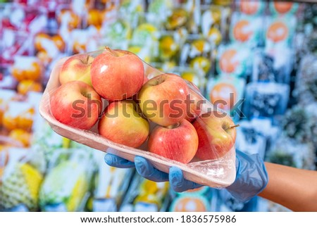 New normal after Covid-19 pandemic: A hand with blue protective gloves holds a plastic wrapped plate with red apples. In background vegetables and fruits counter of a supermarket. Stock photo ©