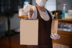 New normal An asian woman, a restaurant staff Gloves and medical face masks are delivering food bags to customers at the restaurant bar to prevent the spread of corona virus.