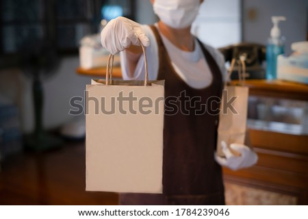 New normal An asian woman wearing gloves and medical face masks delivering take away food bags to customers at the restaurant bar to prevent the spread of corona virus.takeaway concept. space for logo Foto d'archivio ©