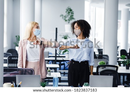 New normal and hello or hi, colleague. Millennial european and black women in protective masks, greet with elbows in morning in interior of coworking office during covid-19 epidemic, empty space