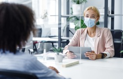 New normal and modern interview during covid-19 outbreak. HR manager with tablet looking for employee, watch at african american woman through protective glass in modern office interior, free space