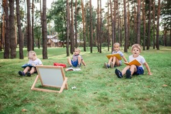 New normal back to school. Kindergarten and elementary scholars sitting on grass at open air class during pandemic. Safe hybrid education, social distance rule, new schooling guidance