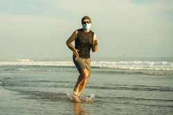 New normal beach jogging workout - young fit and attractive man in face mask running barefoot on sea training after covid19 lockdown feeling free outdoors in healthy lifestyle concept