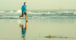 New normal beach running - wide lens view of young fit and attractive man jogging barefoot on sea wearing face mask training after covid19 lockdown feeling free outdoors again