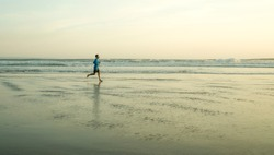 New normal beach running workout - wide lens view of young fit and attractive man jogging barefoot on sea wearing face mask training after covid19 lockdown feeling free outdoors again