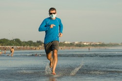 New normal beach running workout - young fit and attractive man jogging barefoot on sea wearing face mask training after covid19 lockdown feeling free outdoors