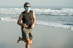 New normal beach running workout - young fit and attractive man jogging barefoot on sea wearing face mask training after covid19 lockdown feeling free outdoors again