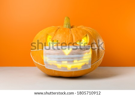 New normal concept. Glowing Halloween pumpkin in a protective medical mask on a orange background. Copy space.
