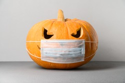 New normal concept. Halloween pumpkin in a protective medical mask on a gray background. Halloween symbol 2020
