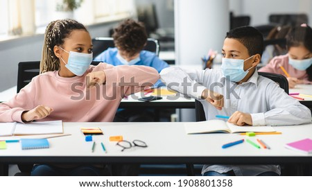 New Normal Greeting. Diverse multiethnic schoolchildren doing elbow bumping sitting together at table and wearing disposable surgical face masks. Black girl and boy avoid coronavirus spread