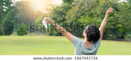 New normal lifestyle, relaxation during Covid-19 concept. Beautiful and wellbeing Asian woman take off medical face mask, raise and open arms, take deep breath of fresh air in park. Health insurance. Photo stock ©