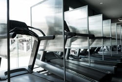 New normal of GYM or FITNESS. Partition beside the electric treadmill to prevent the spread of the disease Covid 19 or Coronavirus. New normal exercise concept.