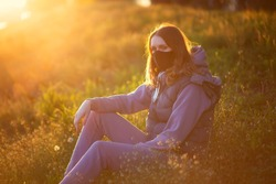 new normal. Portrait of a girl in a mask. Mask mode. Walk in the park. Beautiful sunset summer spring. Nature is an outsider. Quarantine Coronavirus covid19 safety protection