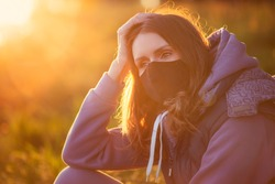 new normal. Portrait of a girl in a mask. Mask mode. Walk in the park. Beautiful sunset summer spring. Nature is an outsider. Quarantine Coronavirus covid19 safety protection. sadness loneliness