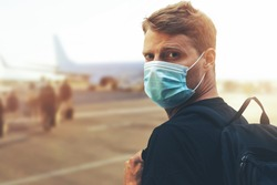new normal, safe travel during coronavirus pandemic - young man wearing protective face mask and boarding plane at airport