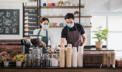 New normal startup small business of coffee shop concept. Male and female barista in face mask and standing behind bar counter in cafe. Young barista wear aprons and check customer order for delivery.