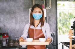 New normal startup small business Portrait of Asian woman barista wearing face mask working in coffee shop while social distancing