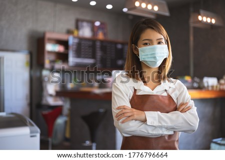 New normal startup small business Portrait of Asian woman barista wearing protection mask stand in her coffee shop while social distancing