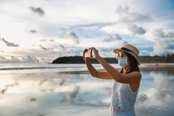 New normal travel concept, Happy traveler asian woman with mask and mobile phone sightseeing in Kata beach, Phuket, Thailand