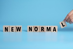 New Normal word on wooden alphabet cube. Concept a new normal life after pandemic.
