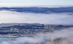New Nuuk city, capital of Greenland photographed from mountaintop, through clouds background