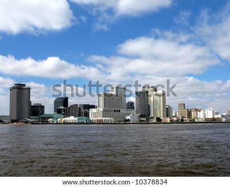 New Orleans Louisiana downtown skyline cityscape of the major hotels area and commercial waterfront across the Mississippi River from Algiers on a sunny day with blue sky