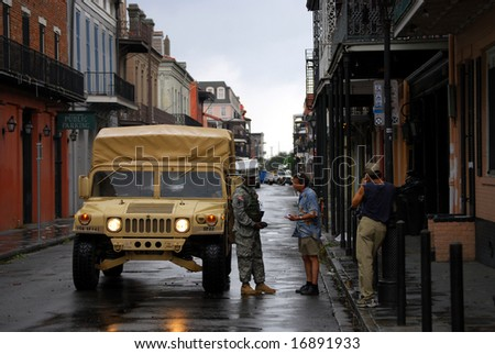 NEW ORLEANS - SEPT 2: A National Guard soldier with a Humvee speaks with a civilian during a curfew after Hurricane Gustav in the French Quarter on September 2, 2008 in downtown New Orleans.