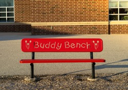 New outdoor buddy red bench for the parents while waiting for kids at a public school playground