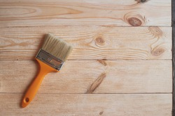 New paint brush on wooden background with place for text, top view,